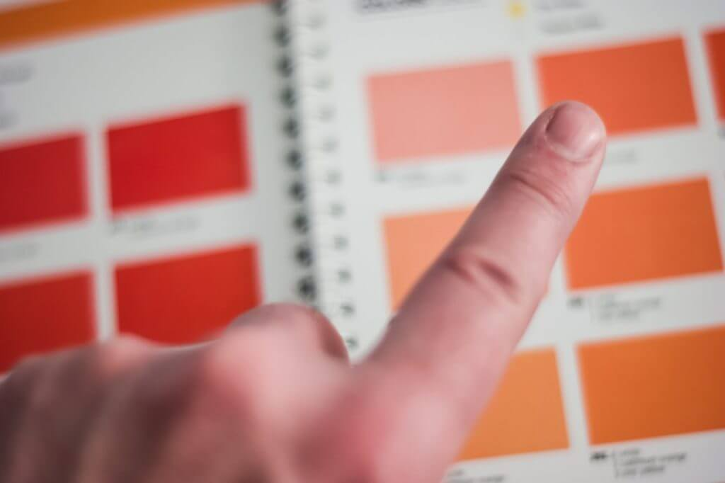 person's finger choosing a color from a book of color options