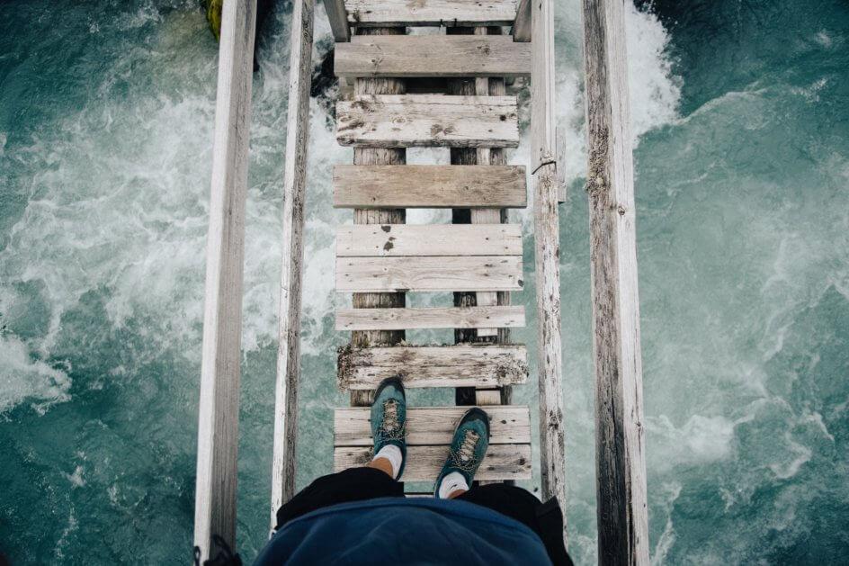Man looking down while walking across wooden bridge