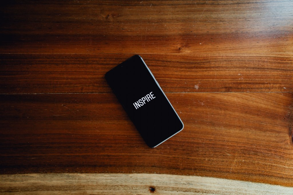 A phone with a wallpaper that says Inspire