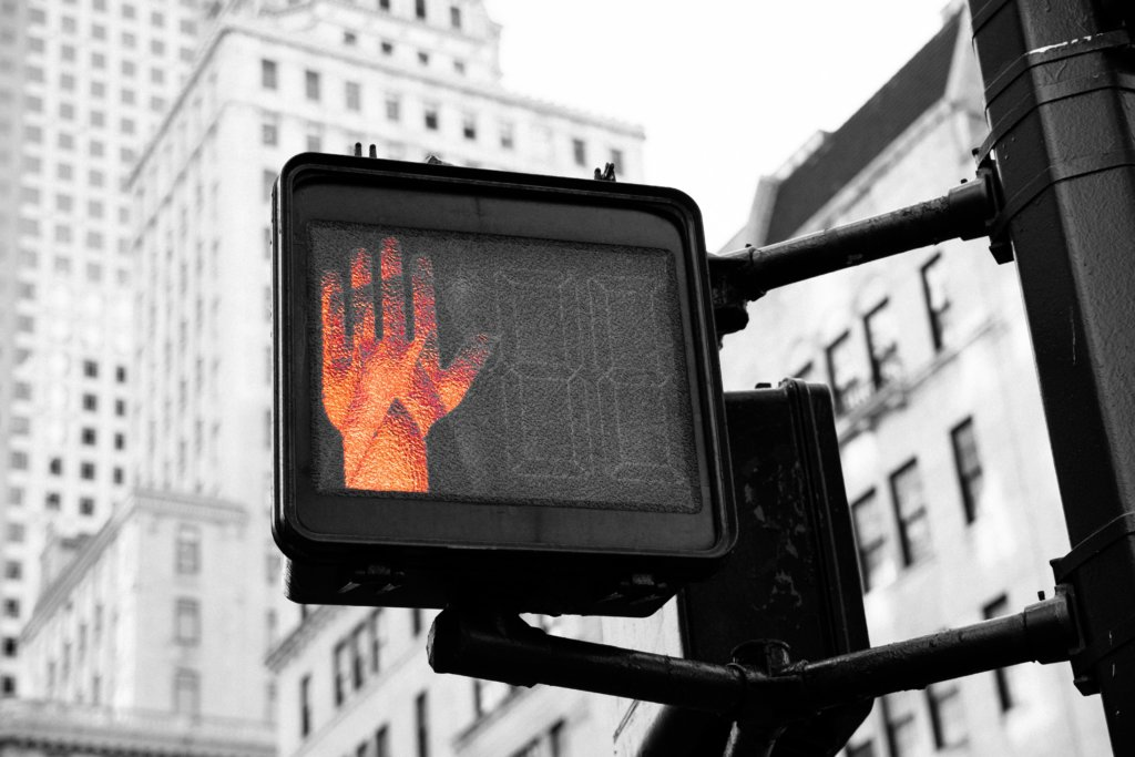 """A cross walk sign with the """"Stop Hand"""" lit up"""