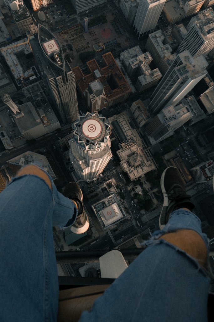 Man dangling his legs off a helicopter while looking down at a city block