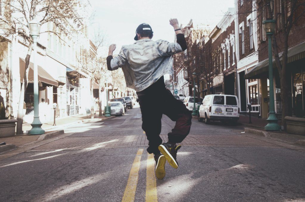 A man jumping and clicking his heels together while walking down a downtown street