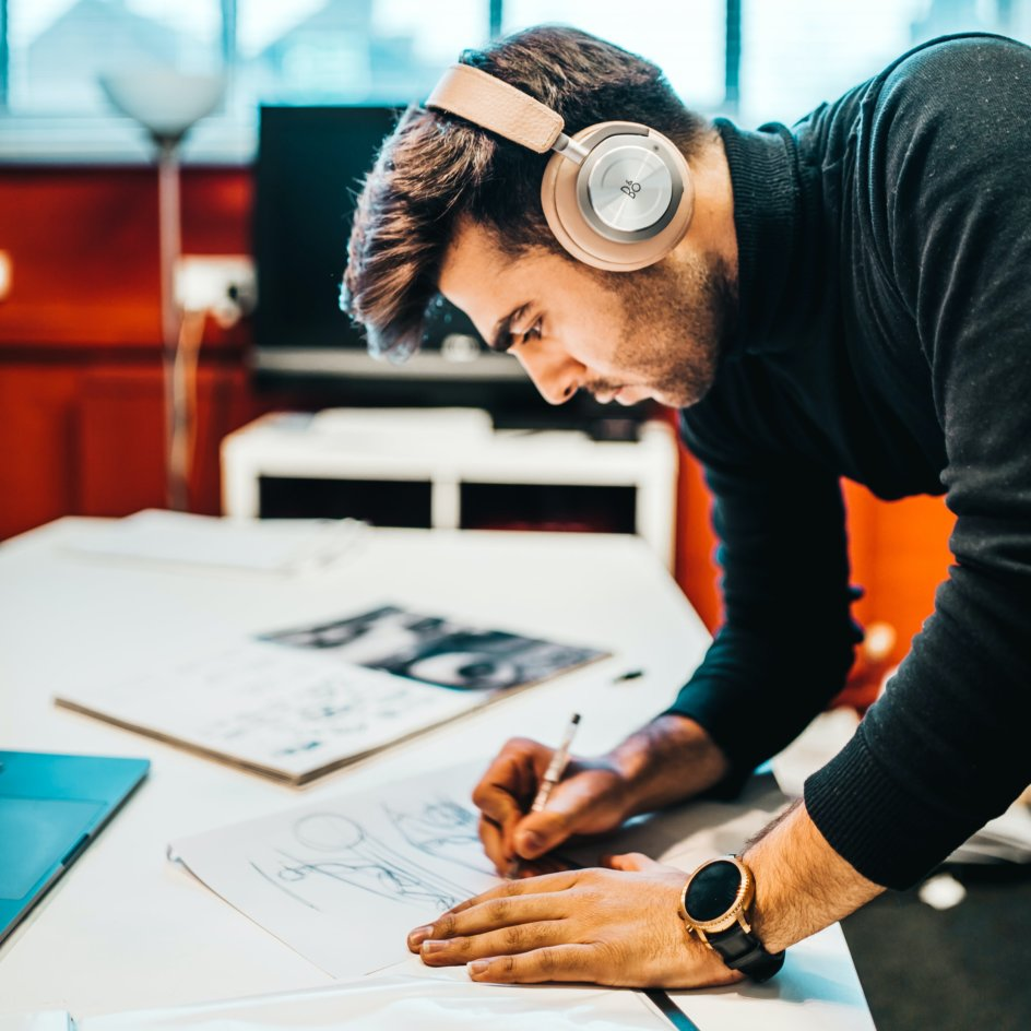 A man with headphones on drawing