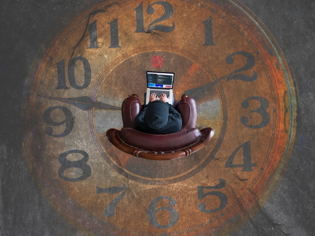 Top-down view of a man working on his laptop surrounded by a giant clock