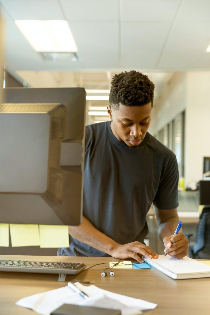 A man writing on a notepad at his desk