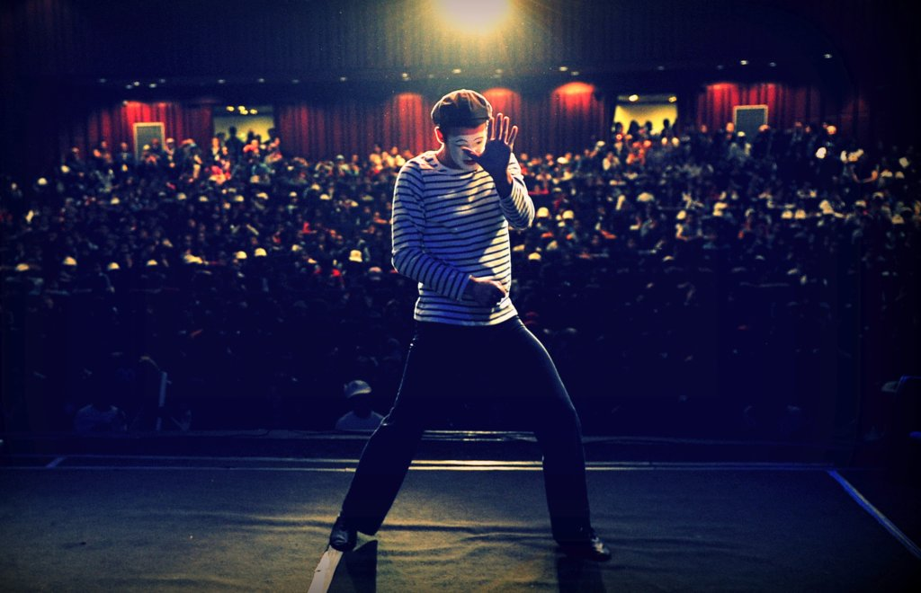 A mime performing on stage in front of a crowd