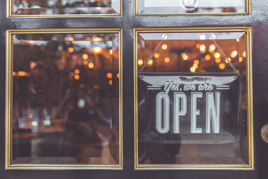 """A window with a sign hanging that says, """"Yes, we are open"""""""