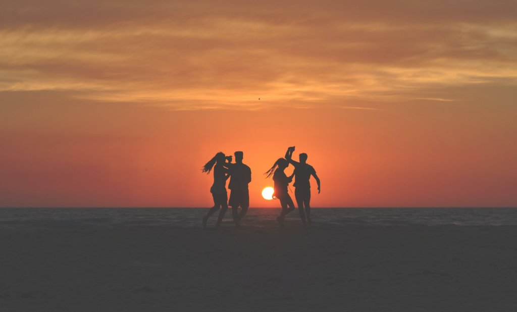 Two couple dancing on the beach with the sun setting in the backgound