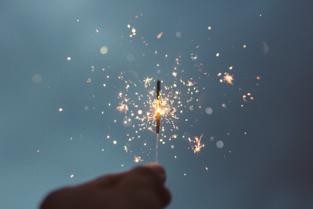 A hand holding a single burning sparkler