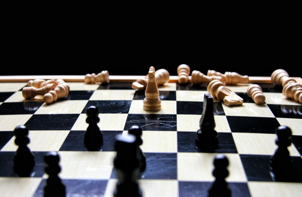 A chess board with one white knight surrounded by black chess pieces