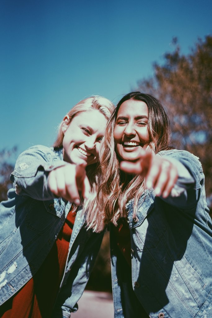 Two girls pointing at the camera and laughing