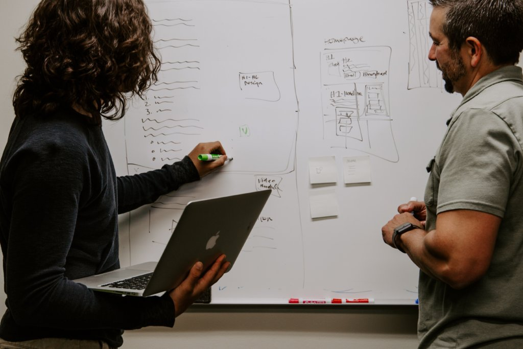 Two people drawing on a whiteboard