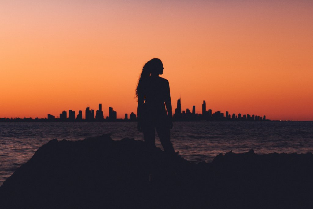 The silhouette of a woman looking into the distance with a sunset skyline behind her
