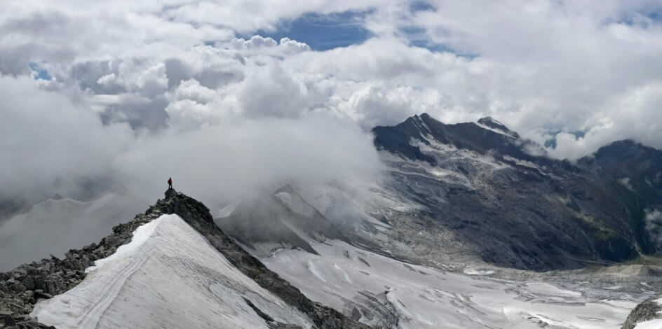 Man standing on a mountain looking at another mountain