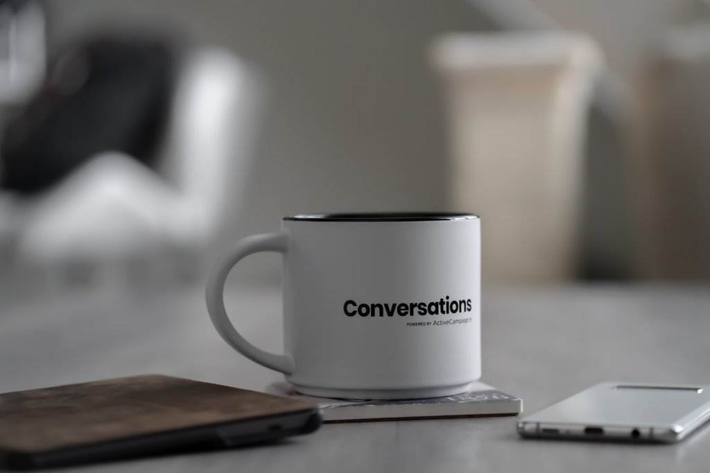 A white coffee mug with the word Conversations printed on it