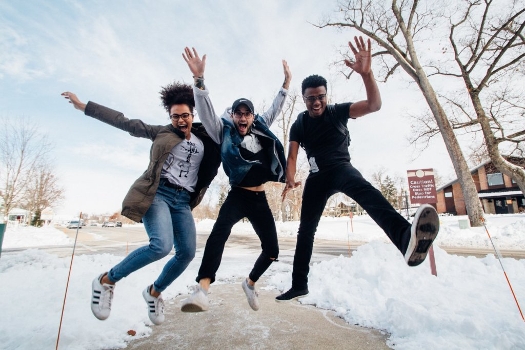 Three humans jumping in the air and looking happy