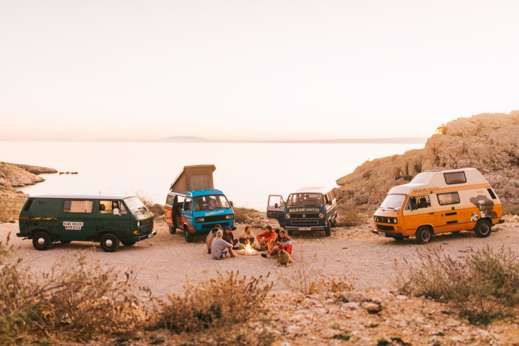 A group of different vans parked with their occupants sitting around a campfire