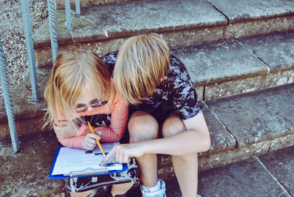 A little boy and girl looking at some papers on a clip board
