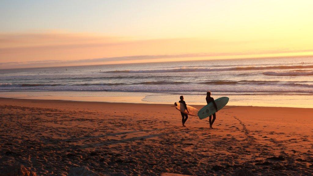 Two surfers walking toward the ocean