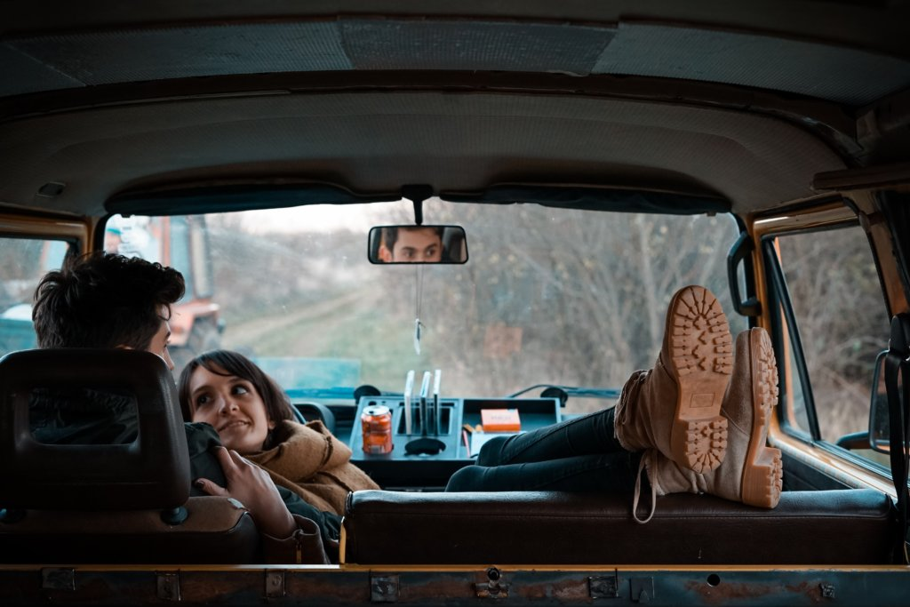 A couple sitting in a van on the side of the road while the woman looks longingly at the man's face