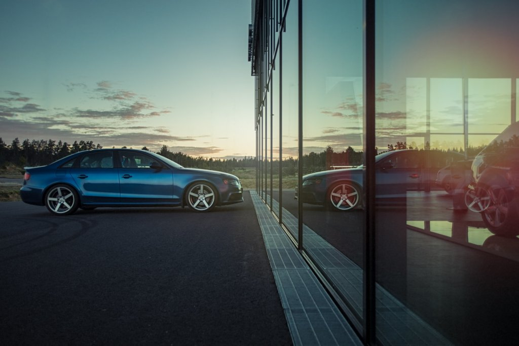 A blue Audi parked in front of a dealership