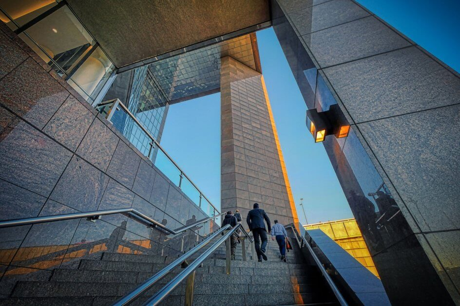 Businessmen walking up a set of stairs outside an office building