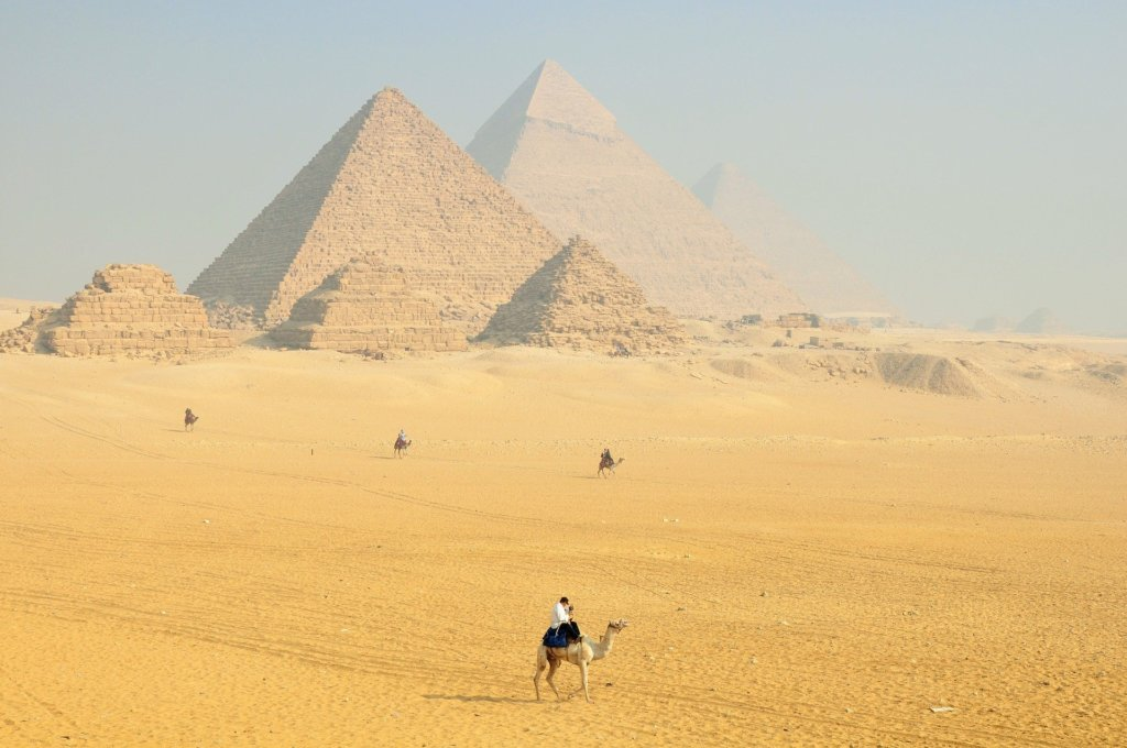 A view of the pyramids of Giza with a few people riding camels in the foreground