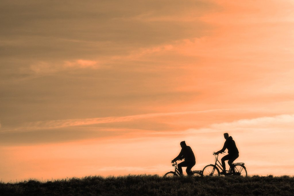 Two people riding bicycles with an orange sky in the background