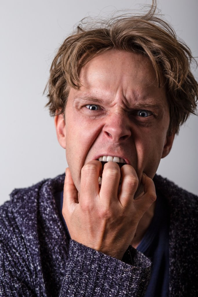 A men so stressed out he's putting his hand in his mouth angrily