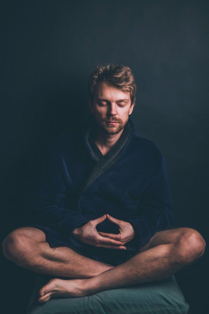 Man meditating in dark blue bath robe