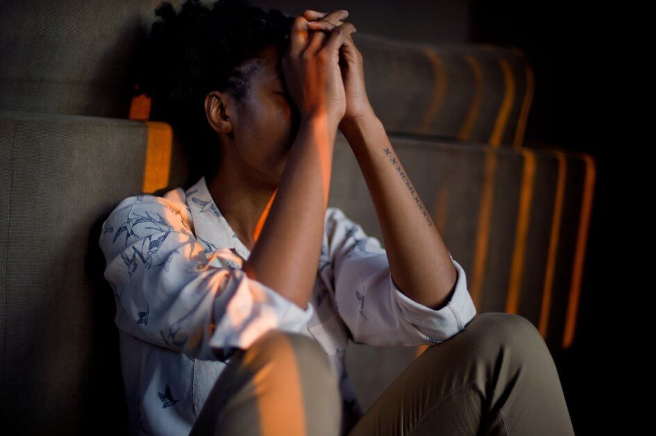 Stressed out woman sitting down with her hands on her forehead