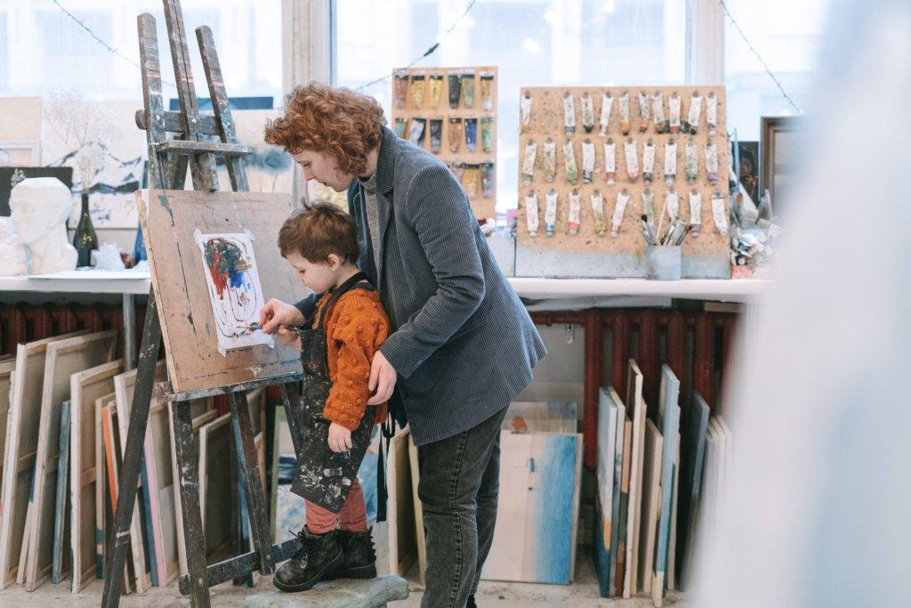 Woman teaching a little boy how to paint
