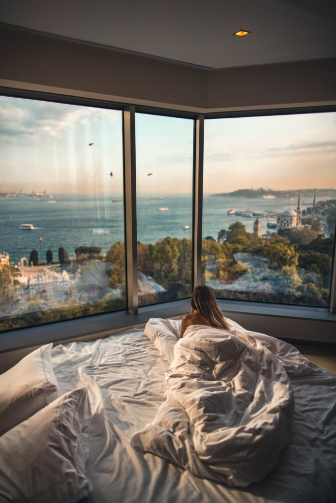 A woman lying in bed looking out over a beautiful ocean view