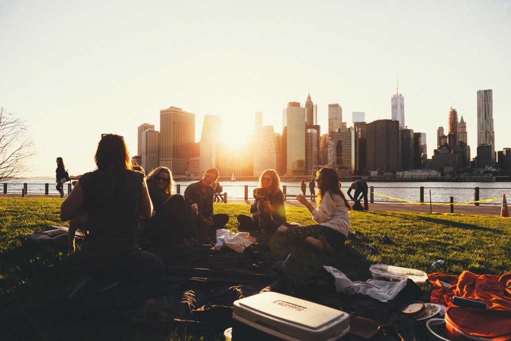 A group of friends enjoying a picnic with a city skyline in the background
