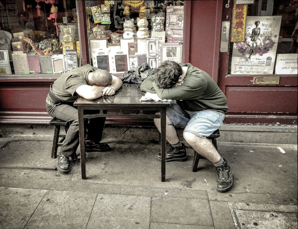 Two men asleep at a table on a sidewalk outside a store