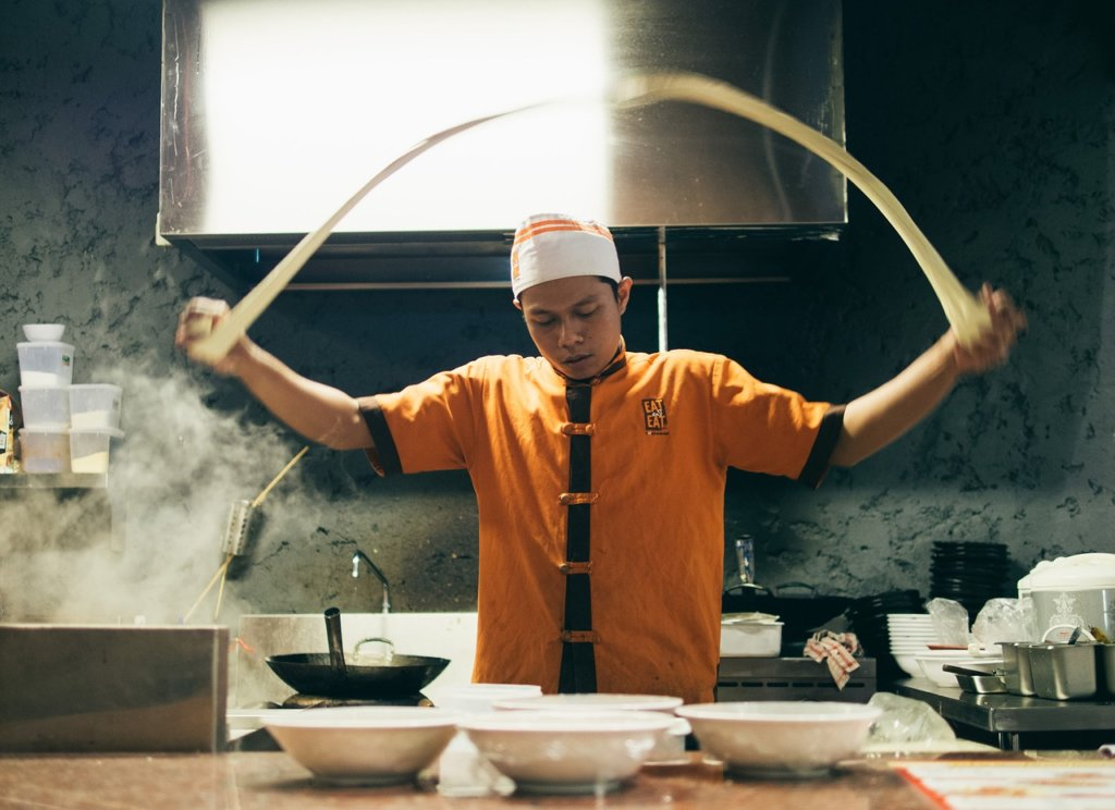 A chef tossing noodle dough into the air