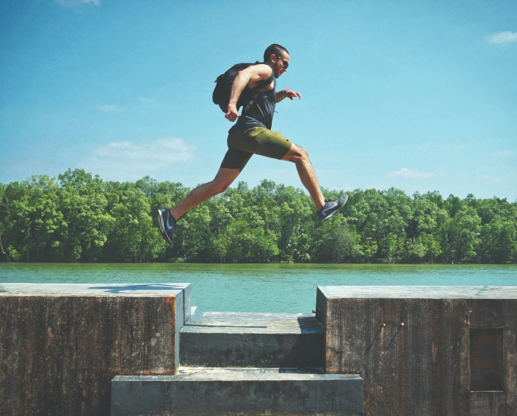 Athletic man jumping from one platform to another