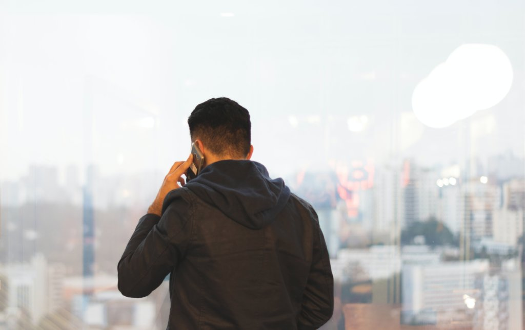 A man talking on his phone with a daytime skyline in the background