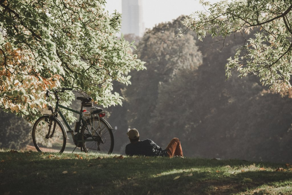 A man resting in a park next to his bicycle