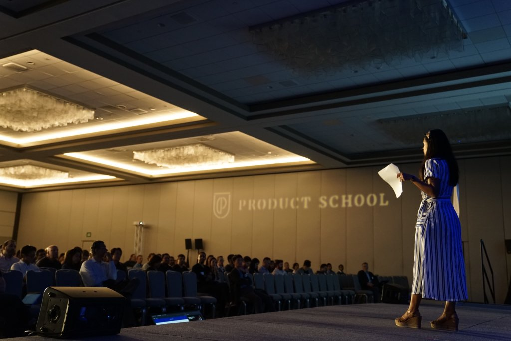 Woman on stage giving a talk to a full auditorium