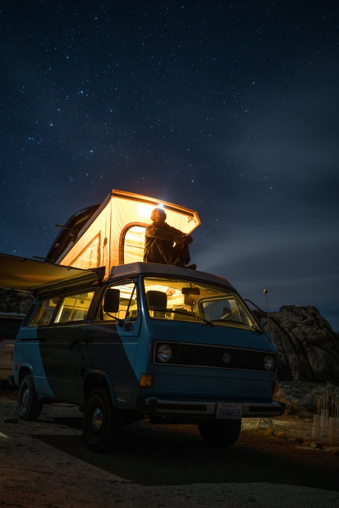 A man sitting on top of his VW camper van and staring up at the night sky